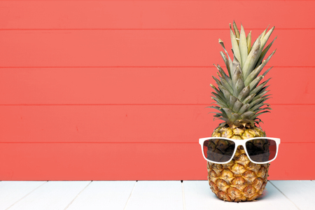 Hipster Ananas mit Sonnenbrille vor einem lebenden korallenfarbenen Holzhintergrund