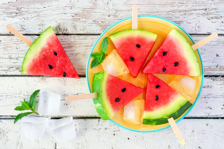Watermelon slice ice cream on a yellow plate against a white wood background Banco de Imagens - 124939954