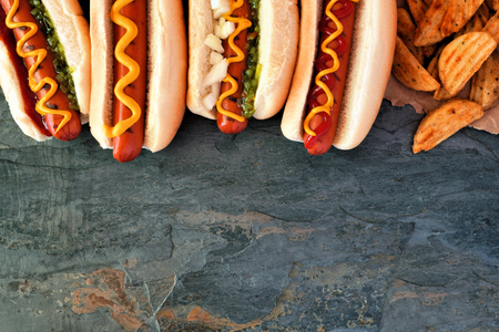 Hot dog top border, overhead view on a dark stone background