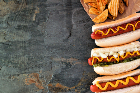 Hot dog side border, overhead view on a dark stone background