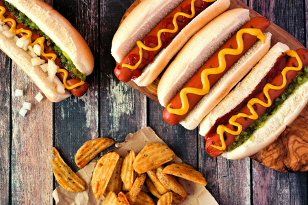 Hot dogs with potato wedges, top view table scene against dark wood