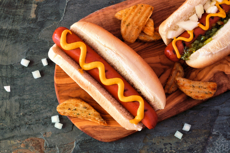 Hot dogs and potato wedges on wooden board, close up, top view