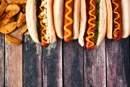 Hot dog top border, overhead view on a dark wood background