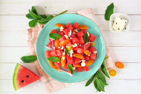 Watermelon and tomato salad, top view on blue plate over white wood