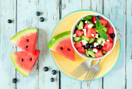 Watermelon salad with cucumber, blueberries and cheese, overhead view scene on blue wood Banco de Imagens