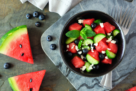 Watermelon salad with cucumber, blueberries and feta cheese, overhead close up scene Stock Photo - 124940547