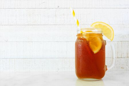 Iced tea in a mason jar glass, side view against white wood
