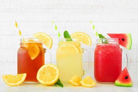 Iced tea, lemonade and watermelon juice summer drinks in mason jar glasses against white wood