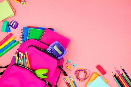 Pink backpack with corner border of school supplies against a pink paper background, top view with copy space Stockfoto