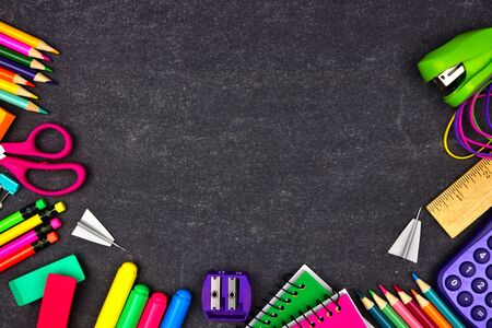 School supplies border frame, top view on a chalkboard background with copy space, back to school concept Фото со стока