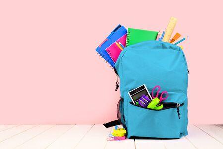 Blauwe rugzak vol schoolbenodigdheden tegen een roze achtergrond, terug naar school concept Stockfoto