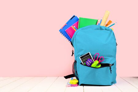 Blue backpack full of school supplies against a pink background, back to school concept