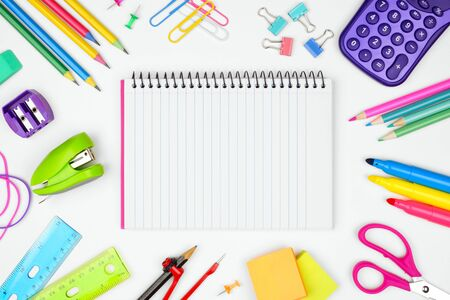 Blank, lined, coil notebook with school supplies frame against a white background, back to school concept