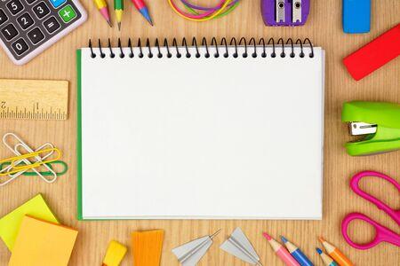 Taccuino a bobina vuota con cornice di materiale scolastico su uno sfondo di scrivania in legno, concetto di ritorno a scuola