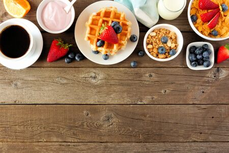 Breakfast food top borde of fruits, cereal, waffles, yogurt and coffee, top view over a dark wood background with copy space
