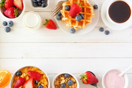 Breakfast food double border of fruits, cereal, waffles, yogurt, milk and coffee, top view over a white wood background with copy space