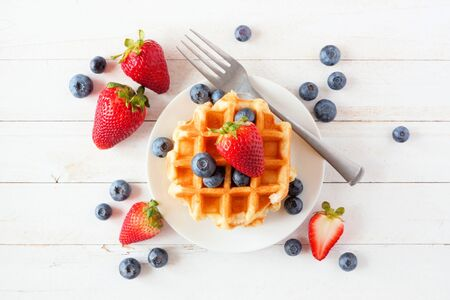 Breakfast waffles with scattered strawberries and blueberries, top view over a white wood background Banco de Imagens