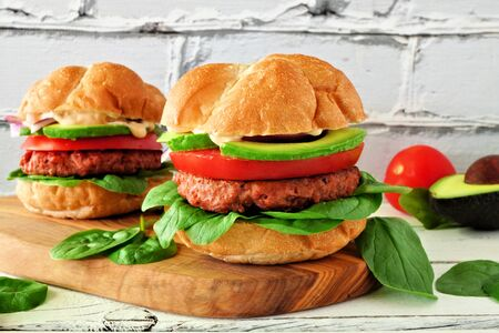 Plant based meatless burgers with avocado, tomato and spinach on a wood serving board against a white brick background