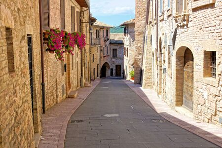 Stone buildings lining a beautiful medieval street in the old town of Assisi, Italy