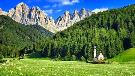 The church of St. Johann under the jagged peaks of the Dolomites during summer, Italian Alps
