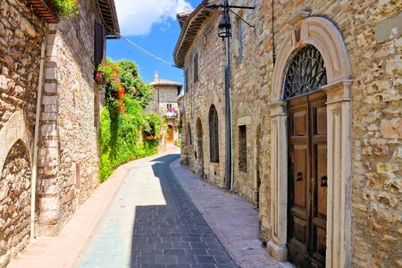 Stone buildings lining a ancient medieval street in the old town of Assisi, Italy