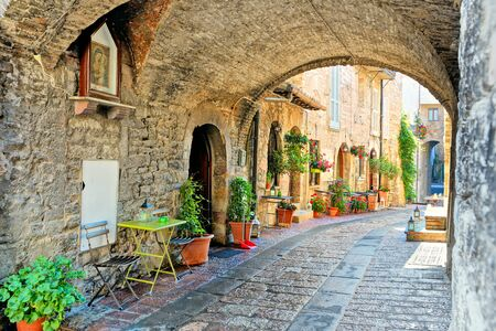 Beautiful arched street in the medieval old town of Assisi with flowers and restaurant tables, Italy