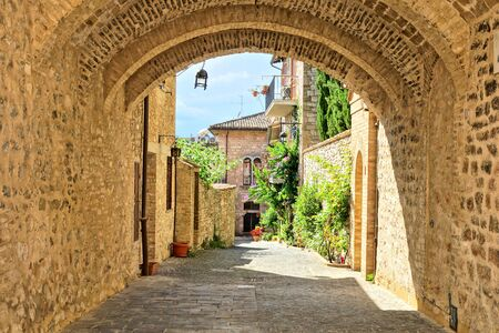 Medieval buildings of the old town of Assisi through a picturesque stone arch, Italy