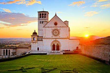 Basilica of San Francis of Assisi with beautiful setting sun behind, Italy Editorial