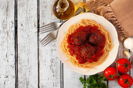 Spaghetti en gehaktballen met tomatensaus, bovenaanzicht hoekrand op een witte houten achtergrond Stockfoto