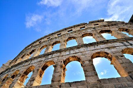 Upward view of the ancient Roman arena in Pula, Croatia under blue skies Banco de Imagens