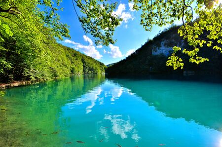 Tranquil blue lakes of Plitvice Lakes National Park, Croatia with overhanging vibrant leaves Banco de Imagens - 128569301