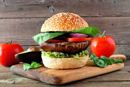 Portobello mushroom vegan burger with avocado, tomato, spinach and onion on a wooden serving board against a dark wood background 版權商用圖片