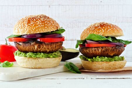 Portobello mushroom vegetarian burgers with avocado, tomato, spinach and onion against a white wood background