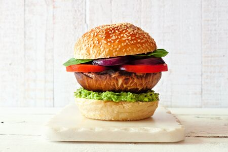Portobello mushroom meatless burger with avocado, tomato, spinach and onion on a marble serving board against a white wood background