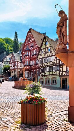 View of the historic Market Square with statue and picturesque half timbered buildings in Miltenberg, Bavaria, Germany 写真素材