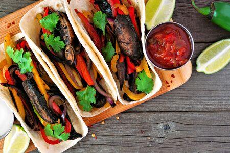 Healthy, plant based meatless portobello mushroom steak fajitas, close up top view on a wood background