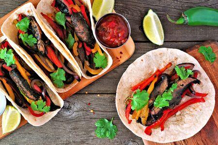 Healthy, plant based meatless portobello mushroom steak fajitas, top view table scene on a wood background