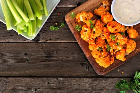 Healthy meatless cauliflower buffalo wings, top view table scene against wood with copy space