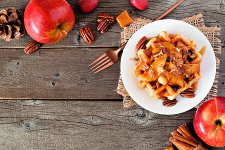 Waffle with baked autumn apples, pecans and caramel, top view corner border with copy space over a wood background