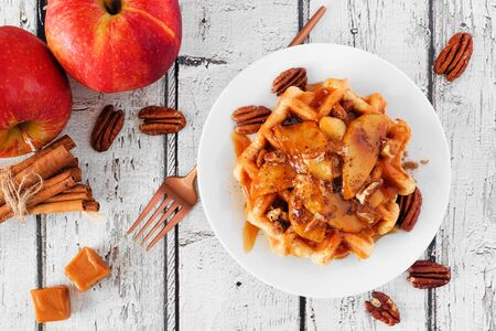 Waffle with baked autumn apples, pecans and caramel, above view table scene over a white wood background