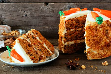 Slice of homemade carrot cake with cream cheese frosting, side view table scene against dark wood