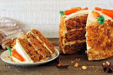 Stück hausgemachter Karottenkuchen mit Frischkäse-Zuckerguss, seitliche Tischszene gegen weißes Holz Standard-Bild