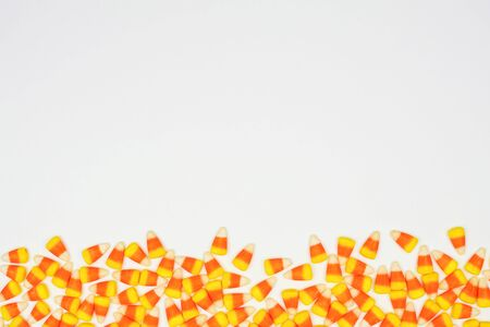 Halloween candy corn bottom border on a white background with copy space