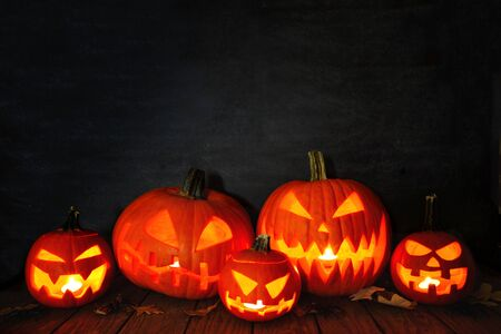 Group of Halloween Jack o Lanterns at night against a dark background