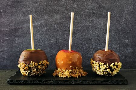 Three types of autumn candy apples with caramel, chocolate and nuts, side view against a slate background Reklamní fotografie