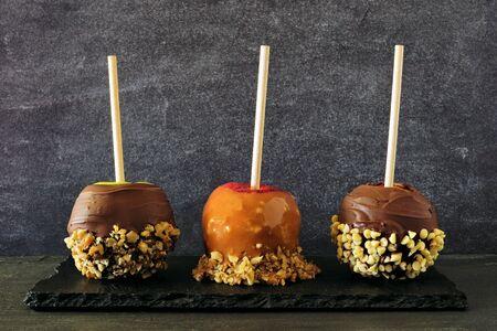 Trois types de pommes bonbons d'automne au caramel, chocolat et noix, vue latérale sur fond d'ardoise Banque d'images