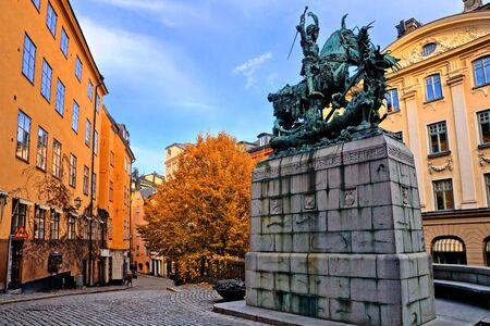 Saint George and the Dragon statue and colorful street during autumn in Gamla Stan, the Old Town of Stockholm, Sweden