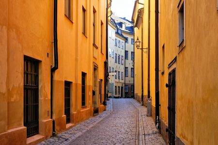 Bright yellow buildings on a narrow cobblestone street in Gamla Stan, the Old Town of Stockholm, Sweden 写真素材