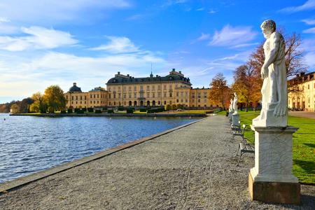 Pałac Drottningholm, szwedzka rezydencja królewska wzdłuż jeziora otoczonego posągami jesienią
