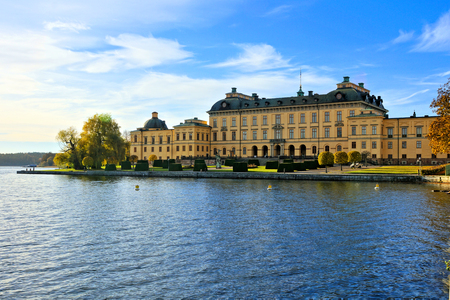 Drottningholm Palace, Swedens royal residence behind lake under blue skies during autumn
